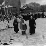 De inwijding van de Maldense St-Antoniuskerk door Mgr. Bekkers op zondag 10 april 1960. Links achter langs de Eendenpoelseweg de boerderij van Jan Broekman voorheen café de Zwaan, middenachter tegenover het huidige cultureel centrum café de Kroon van van Wees, en uiterst rechts de schuur van Piet Sweerts. Rechts van Mgr. Bekkers loopt de Maldense Pastoor C.J. Simons. Op de achtergrond speelt Harmonie Luctor et Emergo 'enkele pittige marsen'.