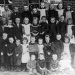 """Schoolfoto bij de oude school in Malden, de schuur van Piet Sweerts, nu """"De Muse"""", Henk Kuik's accordeon winkel en museum. De foto is rond 1900 genomen. No.11 is Piet Nillesen de onderwijzer."""