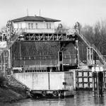 Sluisbrug bij Heumen anno 1960. De brug is gebouwd omstreeks 1925 toen het kanaal z'n voltooiing naderde. Bij de bevrijding van zuidelijk Nederland tijdens operatie 'Market-Garden' in 1944 was deze brug de enige brug over het Maas-Waal kanaal die nog bruikbaar was. De door de aanleg van de S110 overbodig geworden brug is tot spijt van velen in 1990 afgebroken.