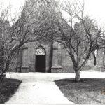 Foto 09-2 R.K. kerk ingang westzijde (JB; Op achtergrond het huis van Poelen)